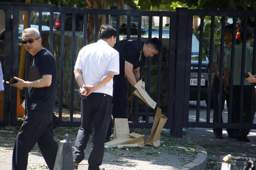 A security personnel removes objects near the US embassy in Beijing on July 26, 2018.