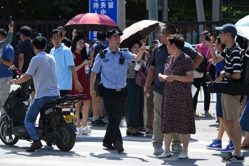 A security personnel gestures among a crowd of bystanders gathered outside the US embassy in Beijing on July 26, 2018.