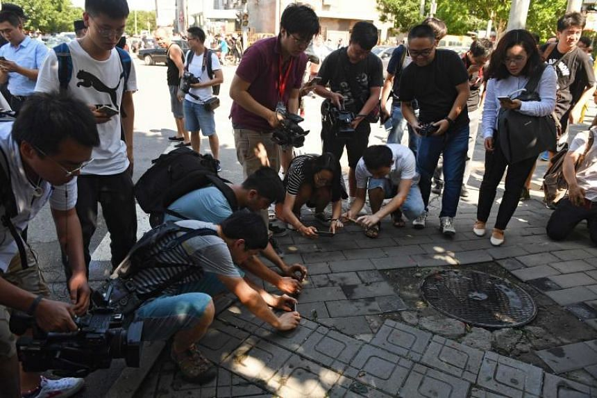Journalists take photos of scattered glass and blood on the pavement outside the US embassy in Beijing on July 26, 2018.