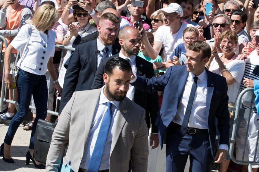 French President Emmanuel Macron, flanked by Elysee senior security officer Alexandre Benalla, greets supporters after having voted in the first of two rounds of parliamentary elections in Le Touquet, France, on June 11, 2017.