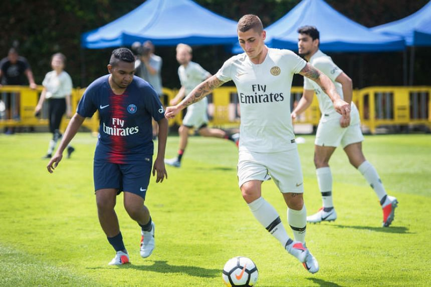 The Straits Times journalist Deepanraj Ganesan (left) ponders to tackle Paris-Saint Germain midfielder Marco Verratti during a friendly match with the media at Geylang Field on July 26, 2018.