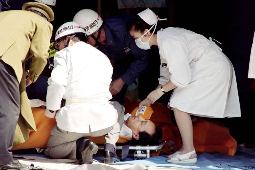 This file photo taken on March 20, 1995 shows a commuter being treated by an emergency medical team after being exposed to sarin gas fumes in the Tokyo subway system.