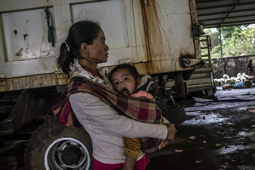 A mother holds her son while waiting for food in a camp for people displaced by a dam failure and flood in Paksong, Laos, on July 25, 2018.