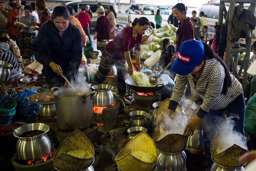 Volumteers prepare meals for displaced residents seeking shelter in Paksong town, Champasak province following massive floodings from the collapsed dam on July 25, 2018.