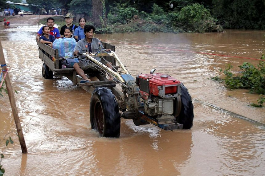 Residents cross flooded areas of Sanamxai, Attapeu province, on July 25, 2018.