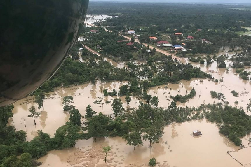 People affected by the flooding crowding around a Lao People's Liberation Army Air Force helicopter delivering relief supplies. An aerial view of the flooded area yesterday after a dam collapsed in Laos' remote Attapeu province on Monday.
