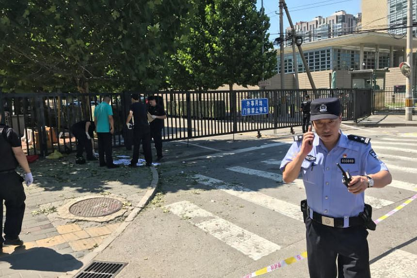 A security personnel gestures near the US embassy in Beijing, China on July 26, 2018.