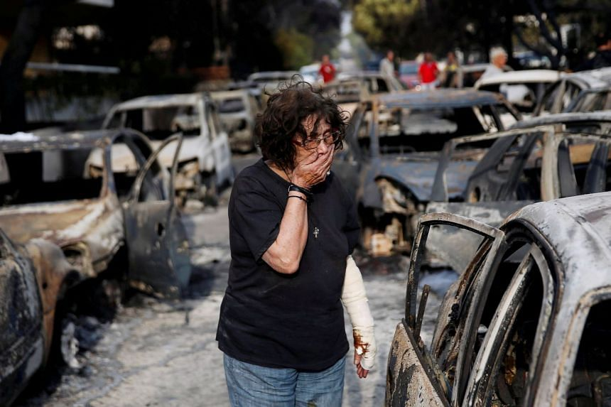 A woman reacts as she tries to find her dog, following a wildfire at the village of Mati, near Athens.