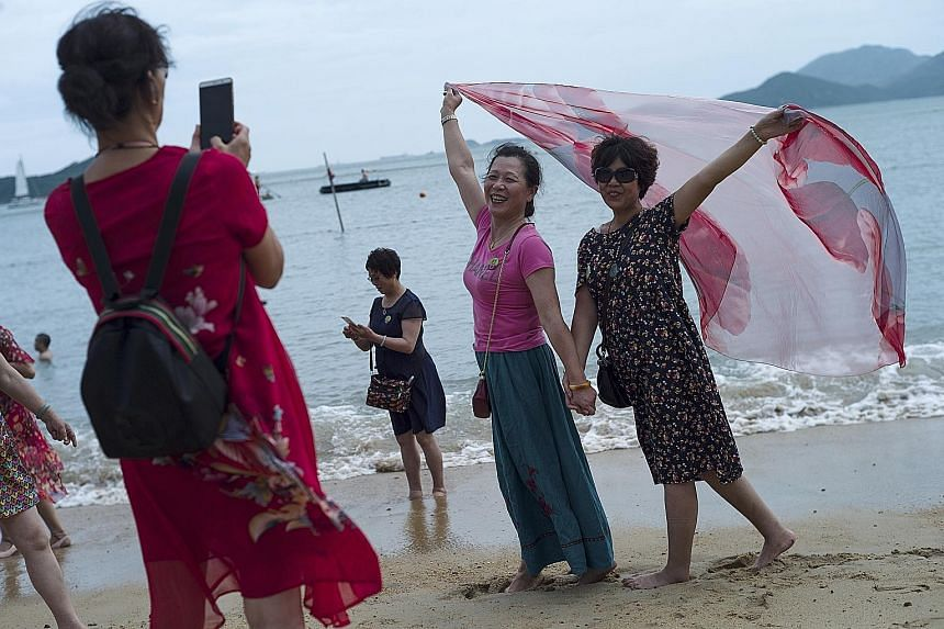 Mainland Chinese tourists on a beach in Hong Kong. Beijing's move to support China's slowing economy has led to a weaker Chinese currency. This, coupled with a strong Hong Kong dollar, could translate into fewer mainland tourists visiting the territo