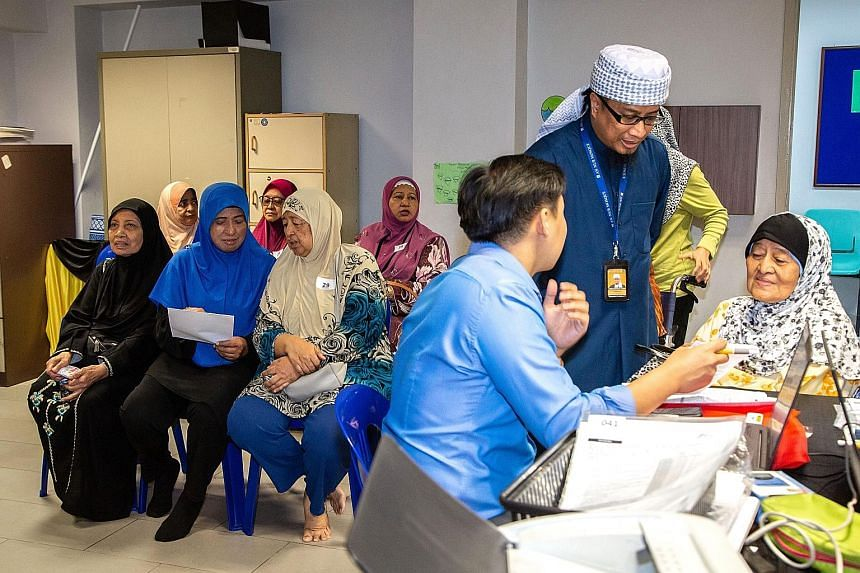 An-Nur Mosque manager Mohd Bahrul-Ulum Buang helping a senior citizen undergoing a medical consultation at the mosque with language translation. About 60 people went for the subsidised health screening on Wednesday.