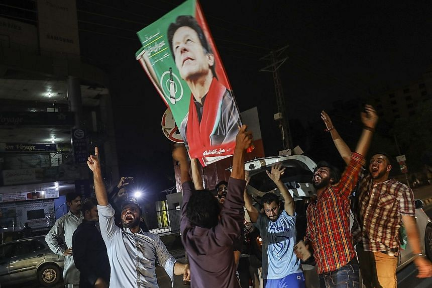 Supporters cheering for Mr Imran Khan on a street in Lahore, Pakistan, on Wednesday. The golden boy who led the national side to its first and only cricket World Cup victory has now been thrown into an unfamiliar place - playing a defensive role as g