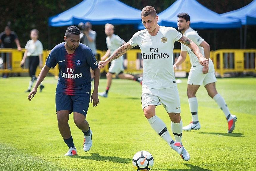 Paris St Germain midfielder Marco Verratti keeps control of the ball while being marked by Straits Times journalist Deepanraj Ganesan in a friendly match between the French champions and the media at Geylang Field yesterday.