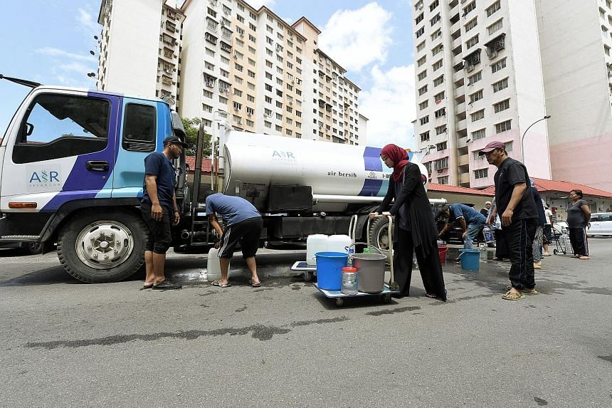 Residents of a Kuala Lumpur apartment block collecting water from a tank after supply was disrupted on March 11. Under a 2006 Act to centralise water infrastructure under the federal government, firms holding water concessions are to sell their asset
