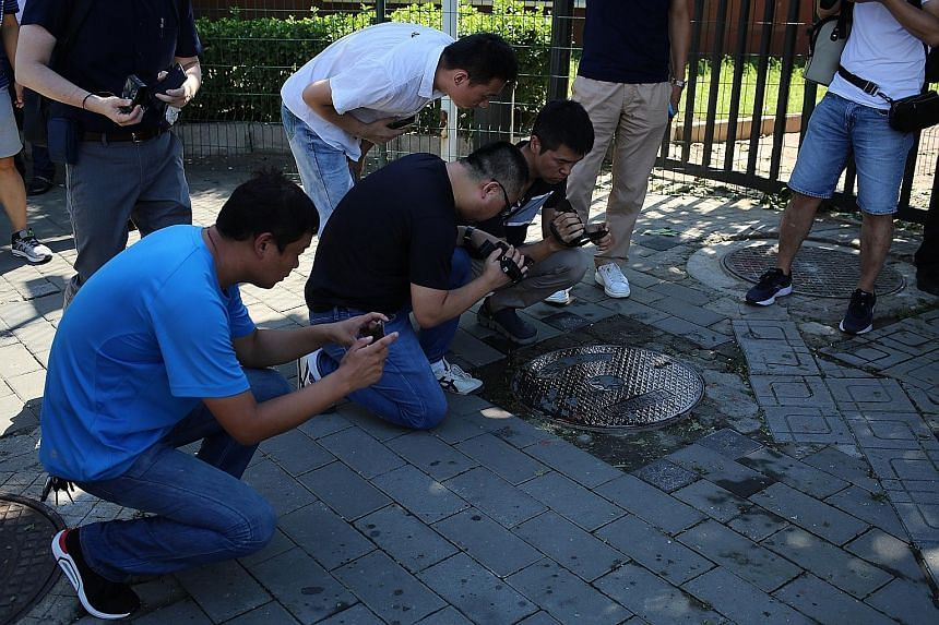 Reporters taking videos and photographs of a blood stain on the ground outside the US Embassy in Beijing following the blast yesterday. An image from a video posted on social media platform Weibo shows the scene immediately after the explosion outsid