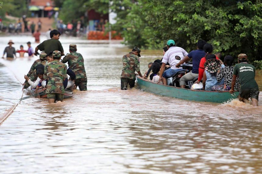 Cambodian soldiers evacuate residents by boat from the floods in Stung Treng province, on July 26, 2018.