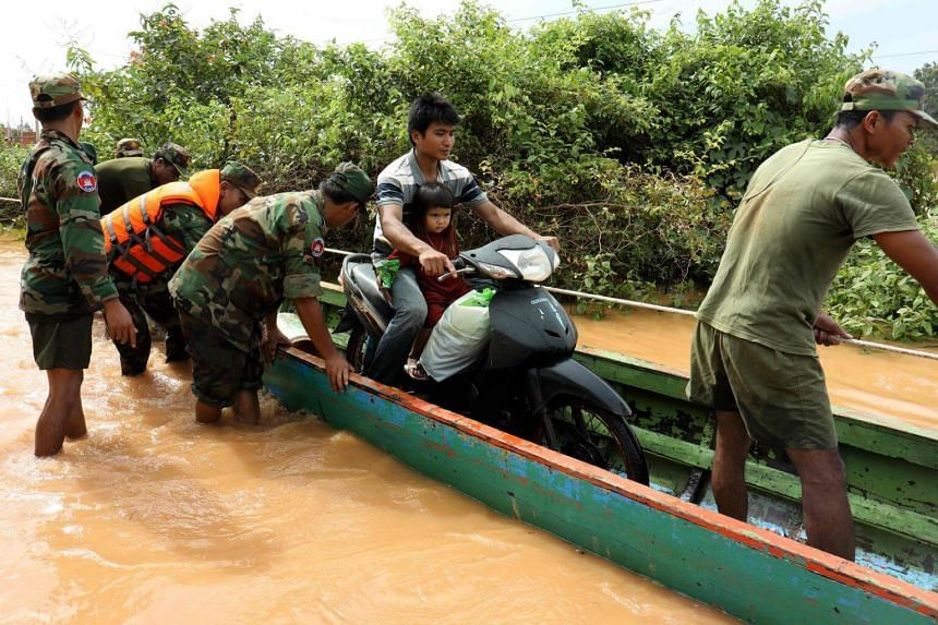 Soldiers helped ferry villagers and their motorcycles to higher ground on wooden boats in Cambodia's north-eastern province of Stung Treng, while supplies were handed out to some who found refuge on dry land.