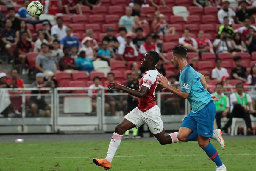 Arsenal's Eddie Nketiah in action against Atletico Madrid's Aitor Punal (right) during the International Champions Cup match between Arsenal FC and Atletico Madrid at the National Stadium in Singapore, on July 26, 2018.