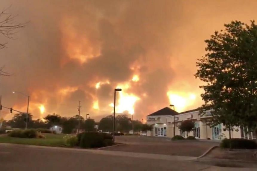 Smoke and flames are seen as a wildfire spreads through Redding, California, on July 26, 2018.