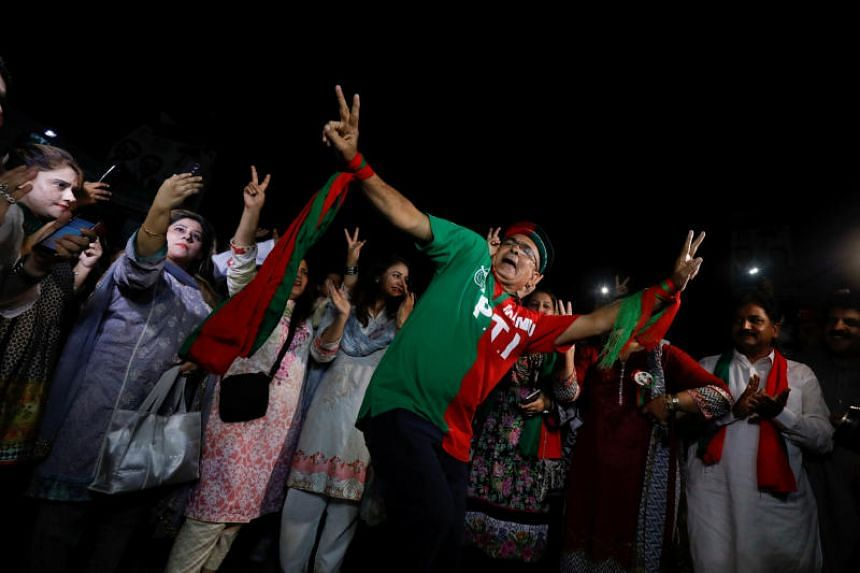 Supporters of cricket star-turned-politician Imran Khan, chairman of Pakistan Tehreek-e-Insaf, celebrate a day after the general election in Karachi on July 26, 2018.