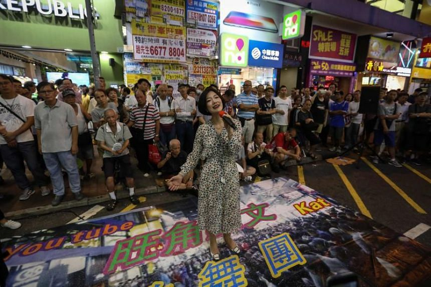 A singer from the Mong Kok Lawman musical troupe performs at Sai Yeung Choi street in the Mong Kok area of Hong Kong on May 26, 2018.