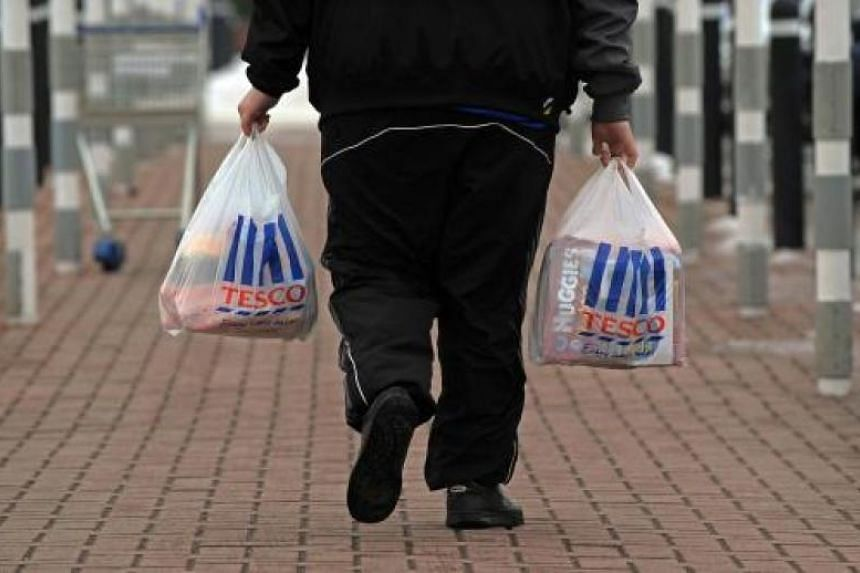 A man walks with shopping from a Tesco supermarket in Birkenhead, north-west England, on Jan 12, 2010.