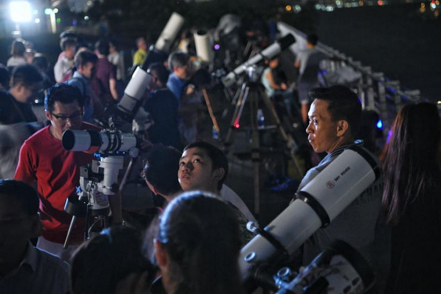 People look through telescopes at the rooftop of the Singapore Maritime Gallery ahead of the total lunar eclipse during a viewing event organised by the Maritime and Port Authority of Singapore and SingAstro community on July 27, 2018.