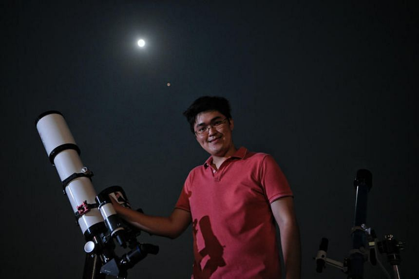 SingAstro member Chin Zong Yang, 26, gets ready to watch the total lunar eclipse on July 27, 2018 with his telescope.