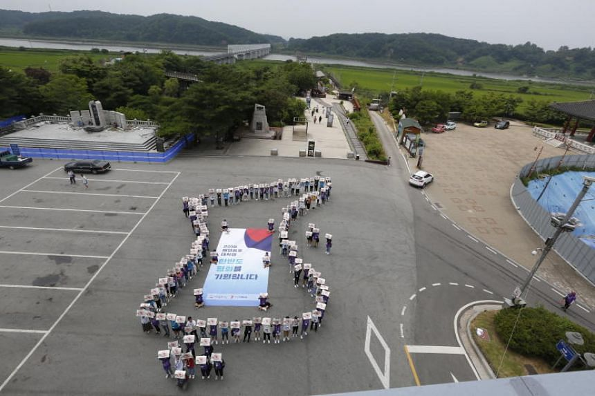 Koreans living overseas stand in the shape of the Korean peninsula for world peace at Imjingak park near the Demilitarized Zone in Paju, South Korea, on July 25, 2018.