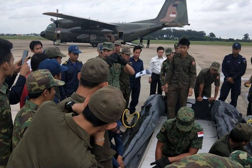 Personnel from the Singapore Combat Engineers and Army Deployment Force teaching Lao People's Army personnel how to use the dinghies for water rescue operations.