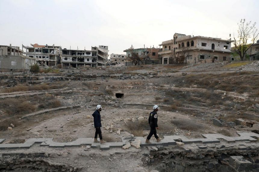 "Members of Syria Civil Defence, also known as the ""White Helmets"", are seen inspecting the damage at a Roman ruin site in Daraa, Syria, on Dec 23, 2017."