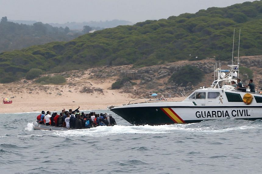 Spanish civil guards try to stop the migrants.