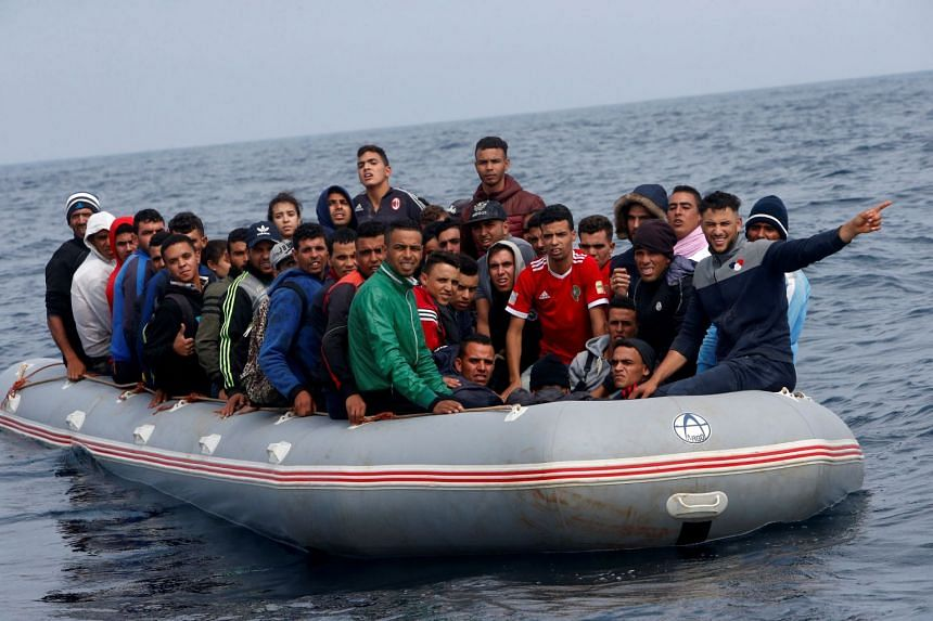 The migrants are seen before disembarking from their dinghy.
