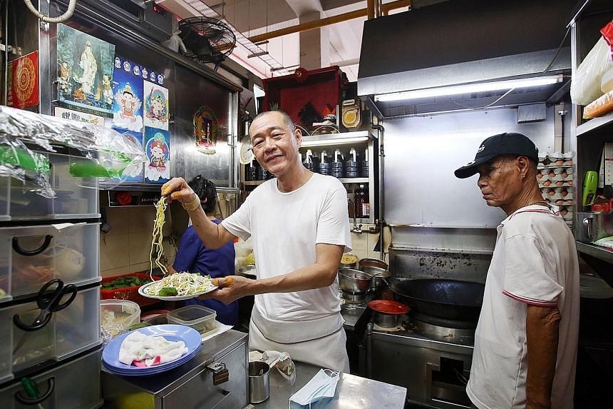 Mr Tan Lee Seng (left) is the owner of Lao Fu Zi Fried Kway Teow in Old Airport Road Food Centre that made it to this year's Michelin Singapore Bib Gourmand list.