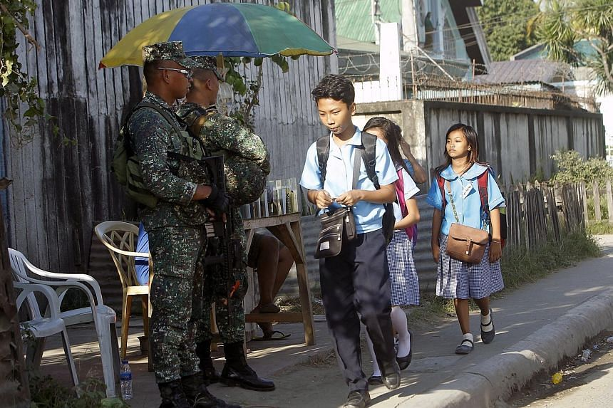 Filipino soldiers standing guard on Thursday in a Muslim area in Zamboanga city, Southern Philippines. President Rodrigo Duterte has signed the Bangsamoro Organic Law granting increased autonomy to Muslims in the south.
