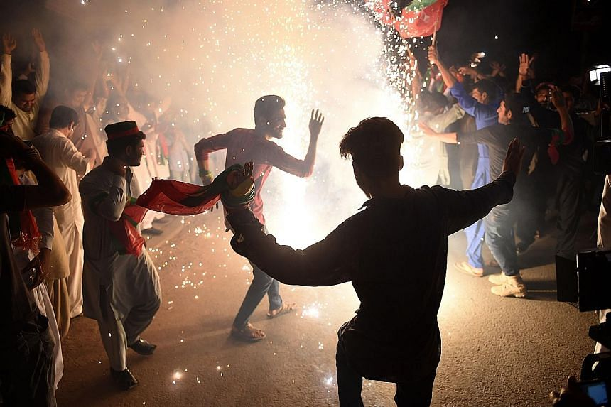Supporters of Mr Imran Khan's Pakistan Tehreek-e-Insaf party celebrating in Karachi on Thursday, a day after the general election. The claims of rigging in the election followed a bitter campaign in which Pakistan's powerful military was accused of t