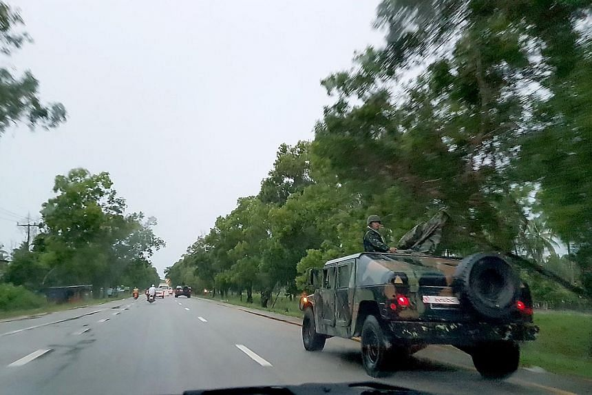 Above: Soldiers in armoured vehicles on the highway to Betong in south Thailand. Left: Members of the National Defence Volunteers Organisation at a checkpoint in Sungai Kolok in Narathiwat province.