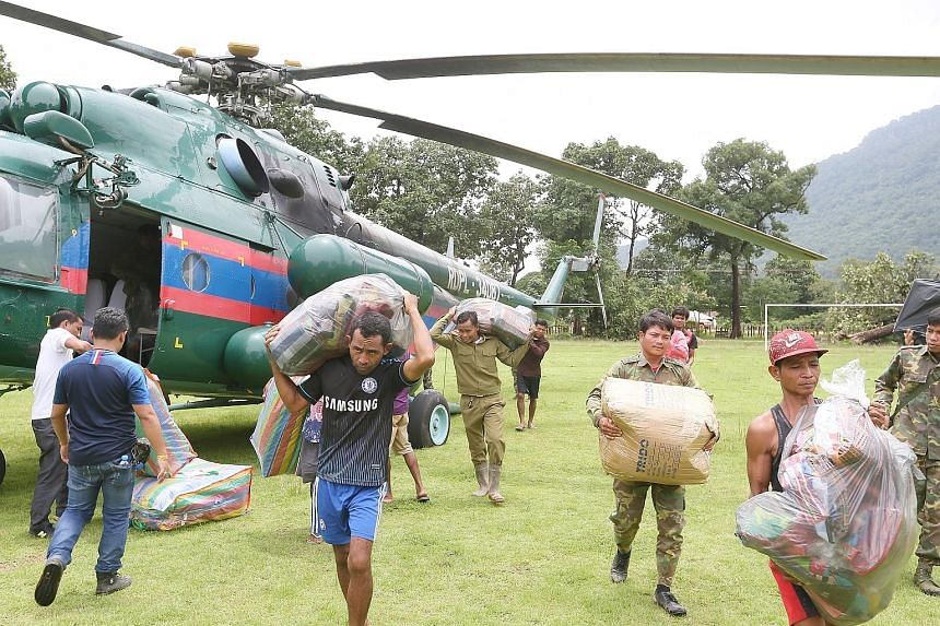 Relief supplies from all around the world are dropped off by helicopters, which land daily on Sanamxai Secondary School's football field. Above: Members of the Thai rescue team helping flood survivors, including a baby trapped in a remote village, cl