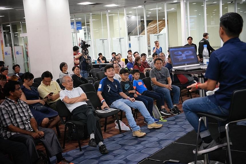 ST sports correspondent David Lee sharing his experiences in Russia with a crowd of 120 at an askST@NLB session (above) and obliging an avid reader with a photograph. The 33-year-old spoke about his challenges in operating on numerous platforms under tigh