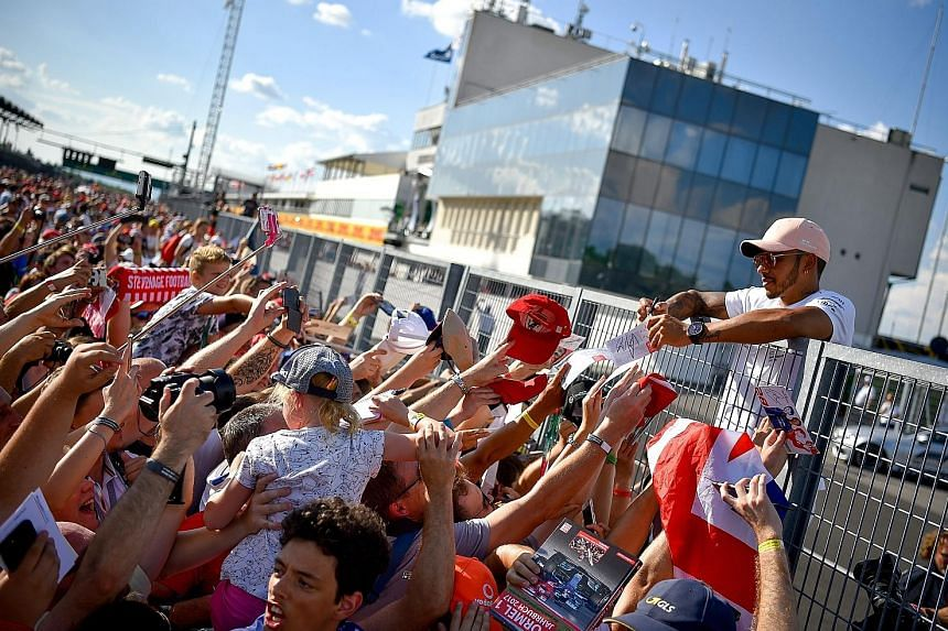 World championship leader Lewis Hamilton signing autographs for fans at the Hungaroring circuit in Mogyorod, north-east of Budapest, on Thursday. The Mercedes driver leads Ferrari's Sebastian Vettel by 17 points.