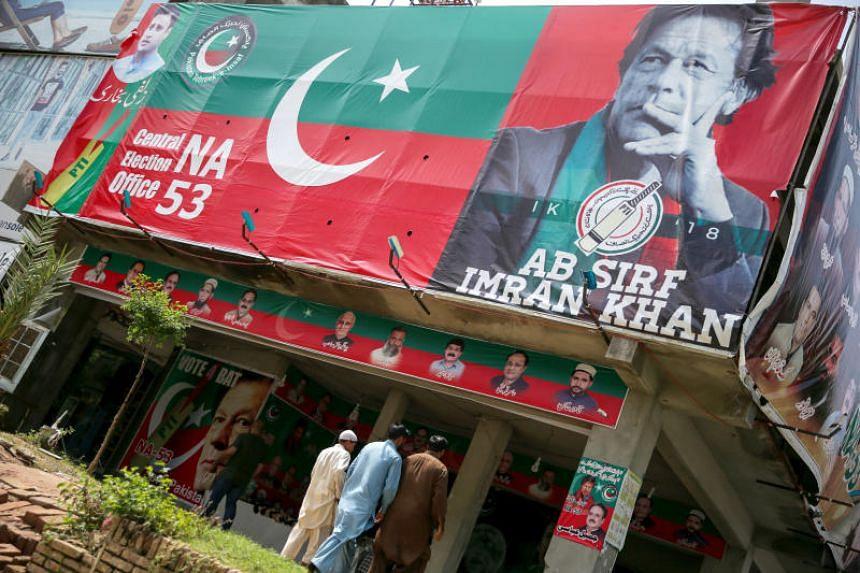 People walk past an image of cricket star-turned-politician Imran Khan, chairman of Pakistan Tehreek-e-Insaf at a market in Islamabad, Pakistan, on July 27, 2018.