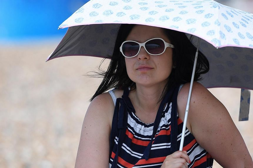A woman shading herself from the sun in Britain, where temperatures are expected to reach close to 36 deg C.