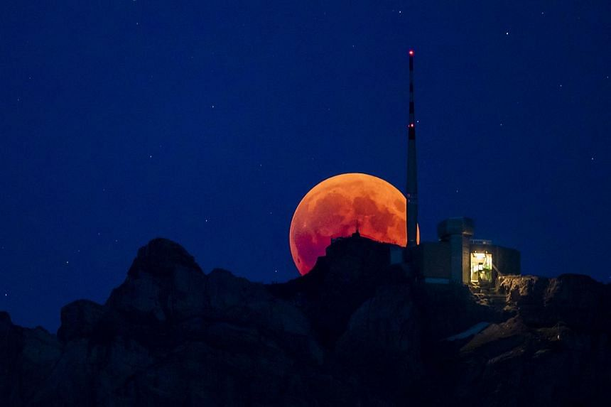 The blood moon rises behind the Saentis Alpstein, Canton of Appenzell, in Switzerland, on July 27, 2018.