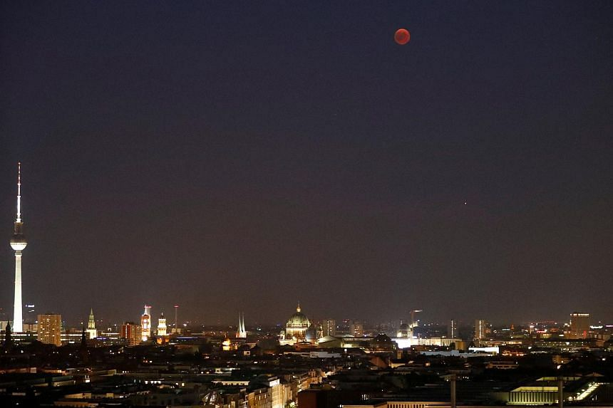 The moon and the mars are seen during a lunar eclipse is seen above the cityscape and the television tower in Berlin, Germany, on July 27, 2018.