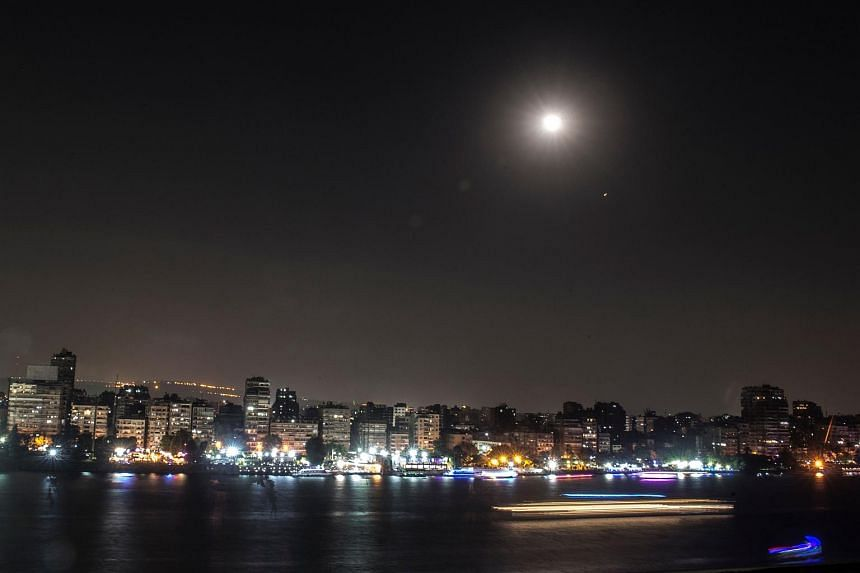 The lunar eclipse is seen in the Egyptian capital of Cairo, on July 27, 2018.
