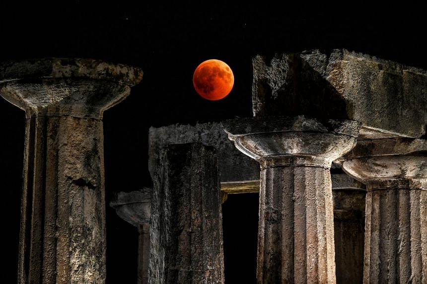 """The full moon is seen during a """"blood moon"""" eclipse over the temple of Apollo in Corinth, on July 27, 2018."""