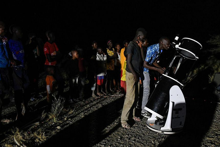 """People looking through a telescope at a """"blood moon"""" eclipse in Oloika town in Magadi, Kenya, on July 27, 2018."""