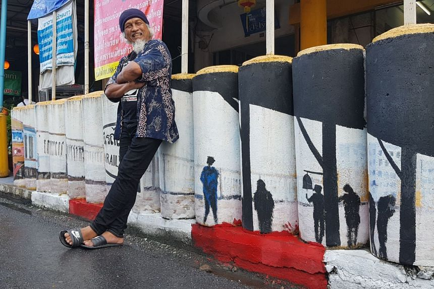 Ethnic Malay artist Waearong Waeno with his artwork depicting a scene at Yala Railway Station on the bollards which buffer shopfronts from car bombs.