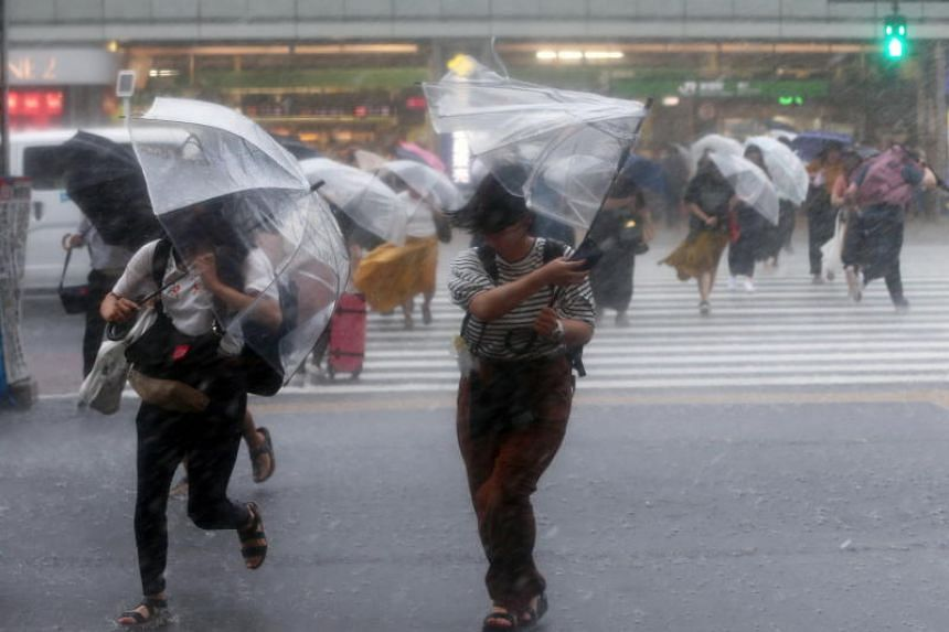 Pedestrians crossing a road struggle against the strong wind and rain in Tokyo, Japan, 28 July 2018, as Typhoon Jongdari is expected to make landfall in central Japan. Residents in flood-devastated western Japan have been warned to evacuate as soon a
