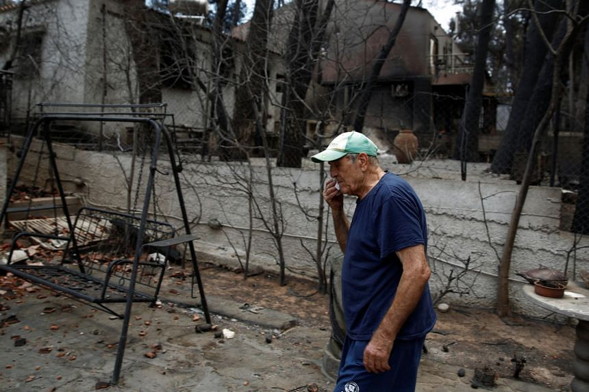 A man wipes his face while standing in the yard of his burnt house, July 28, 2018.