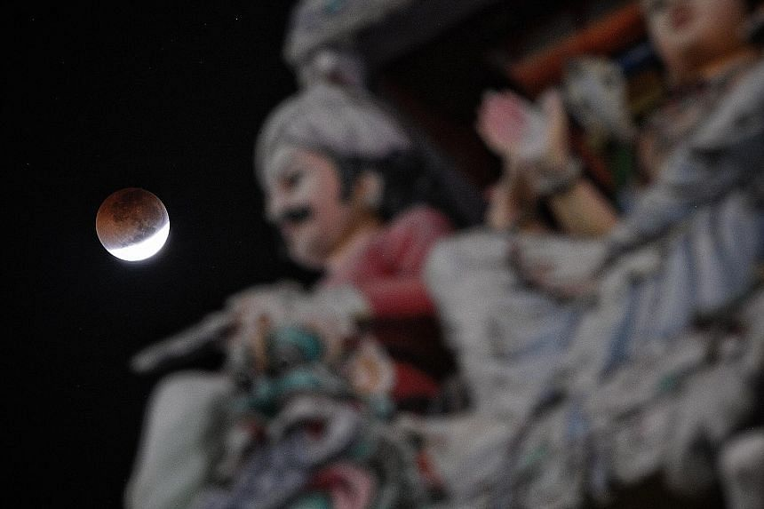 Stargazers at a viewing event on the rooftop of the Singapore Maritime Gallery at Marina South Pier on Friday night. The Moon seen over Sri Mariamman Temple in South Bridge Road, minutes before the beginning of a total lunar eclipse at 3.30am yesterd